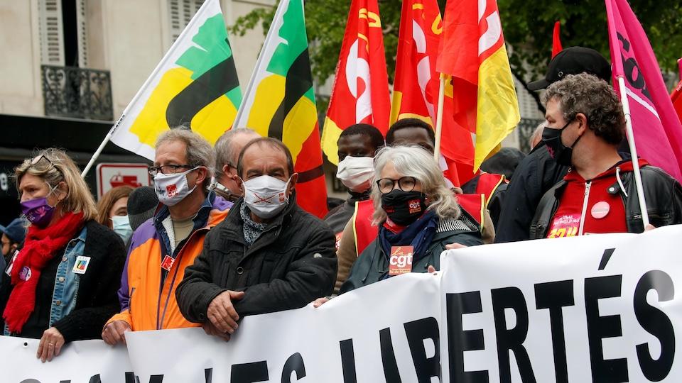 Des manifestants masqués portent des banderoles.