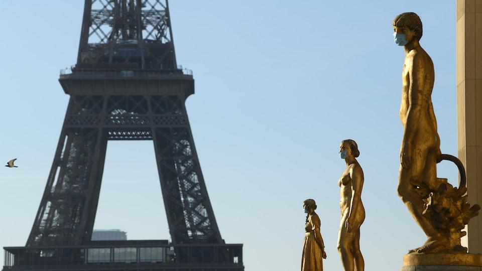 Des statues à la place du Trocadéro à Paris portent des masques médicaux.