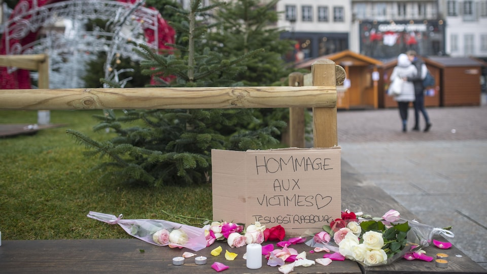 STRASBOURG, FRANCE - DECEMBER 12: Flowers, candles and a sign 'Hommage aux Victimes' pictured at the Christmas market where the day before a man shot 14 people, killing at least three, on December 12, 2018 in Strasbourg, France. Police have identified the man as Cherif Chekatt, a French citizen on a police terror watch-list. Chekatt exchanged gunfire with soldiers after the attack, is reportedly injured and is still on the loose. (Photo by Thomas Lohnes/Getty Images)