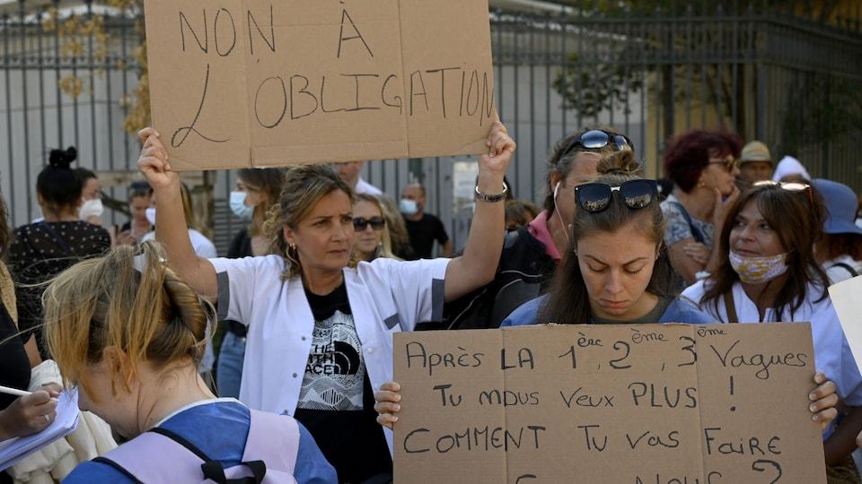 Des manifestants tiennent une affiche sur laquelle il est écrit : non à l'obligation vaccinale.