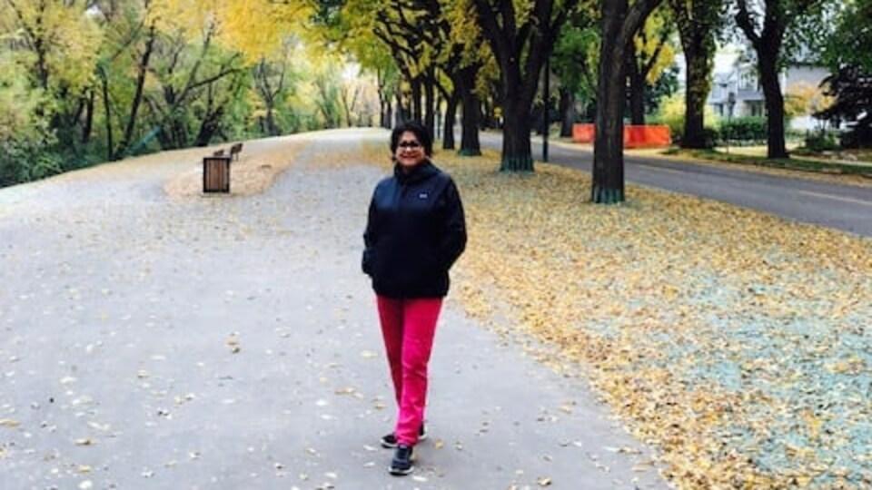Frances Sreedhar sur un chemin bordé d'arbres à l'automne avec les feuilles qui ont commencé à tomber.