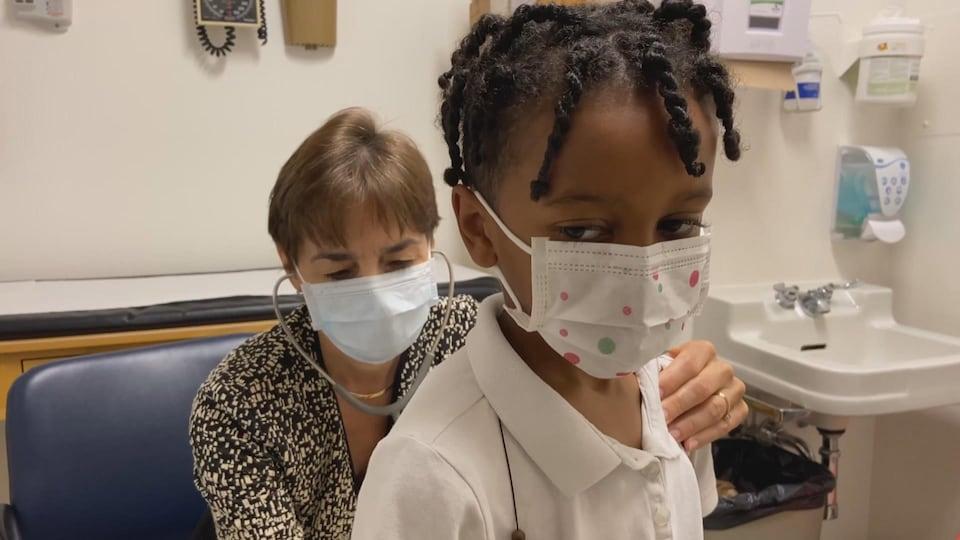 La médecin écoute l'enfant respirer.