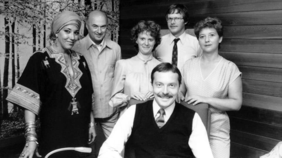 En studio, l'équipe de Montréal-Express : la chroniqueuse culturelle Francine Grimaldi, le technicien Bernard Lamarche, la réalisatrice Lorraine Saey, un homme non identifié et la météorologue Jocelyne Blouin entourant l'animateur Michel Desautels, assis.