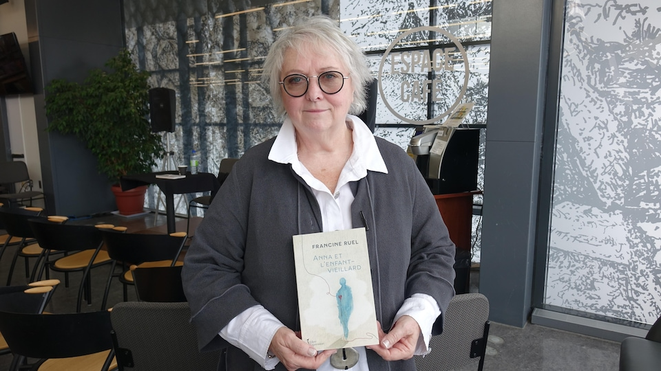 Elle pose avec son livre dans les mains.