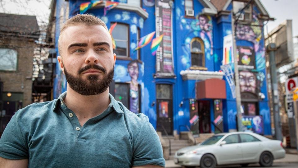 Un jeune homme pose devant le bar Crews and Tango, dans le village gai à Toronto.
