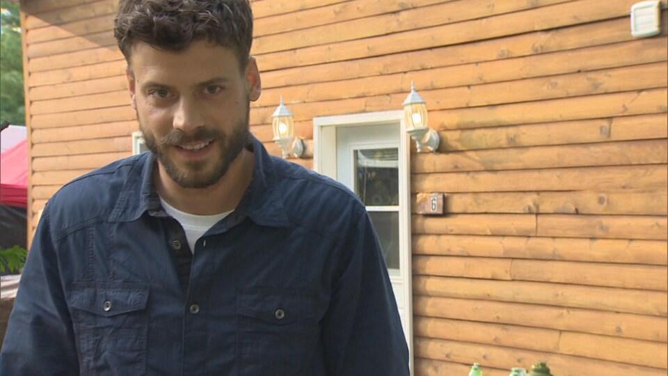 François Arnaud est debout devant une maison en bois et fixe l'objectif de la caméra.