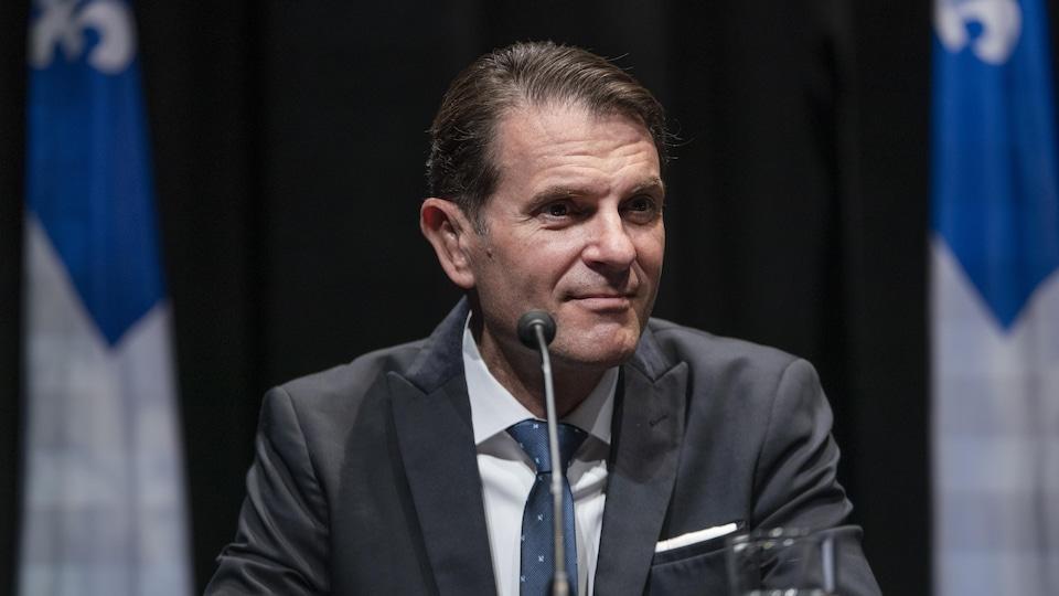 Le ministre des Transports, François Bonnardel, assis durant une conférence de presse.
