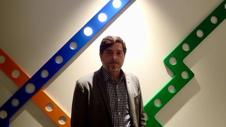 François Chamberland, directeur exécutif Ingénierie, Infrastructures et Projets Majeurs de la STM. Il pose devant une carte géante du métro de Montréal.