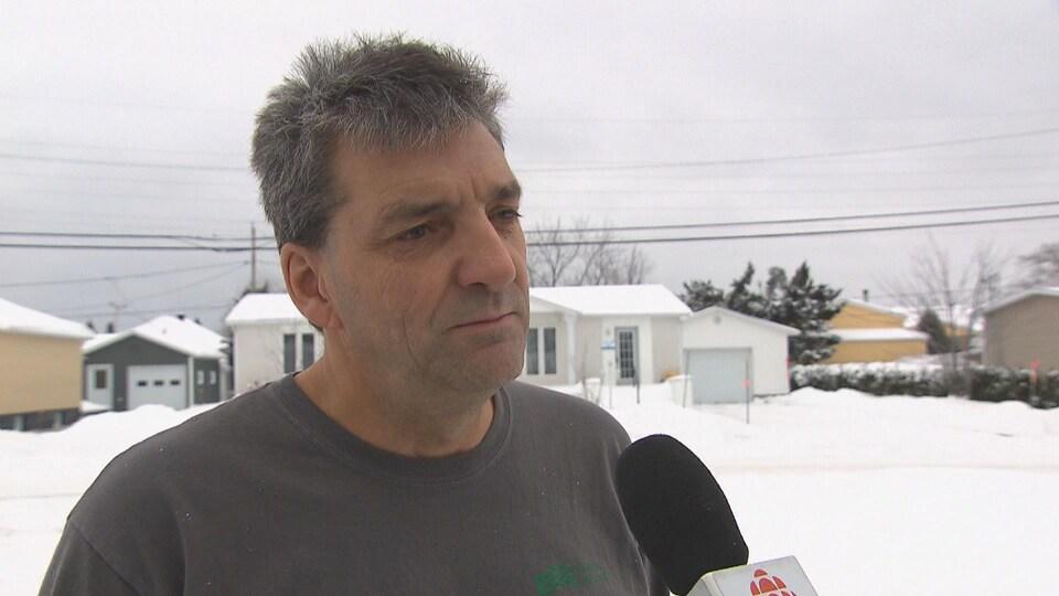 Un homme donne une entrevue à Radio-Canada. Il est dehors dans sa rue.