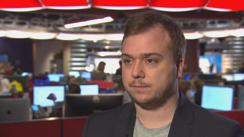 Un homme devant des écrans d'ordinateurs