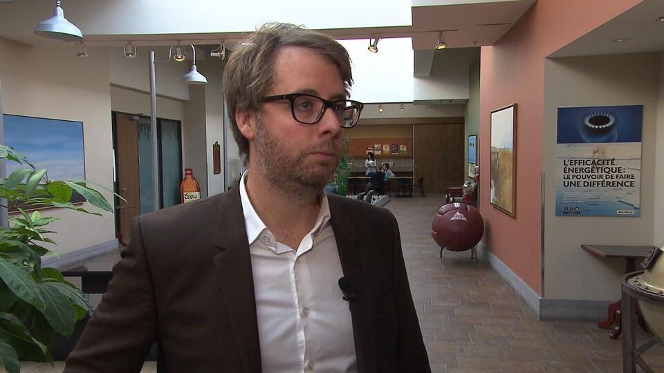 François Lefebvre porte des lunettes et un veston.