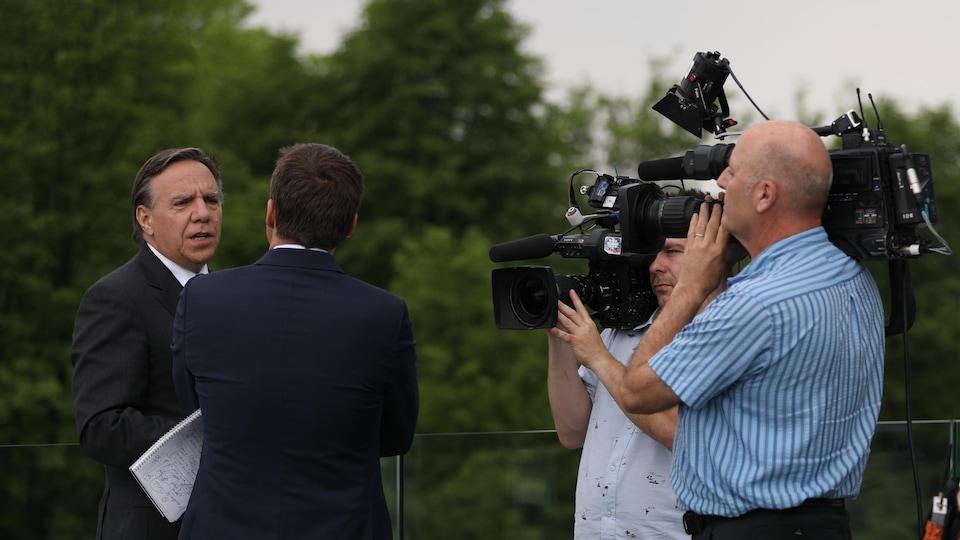 François Legault en entrevue, entourés de 2 caméramans.
