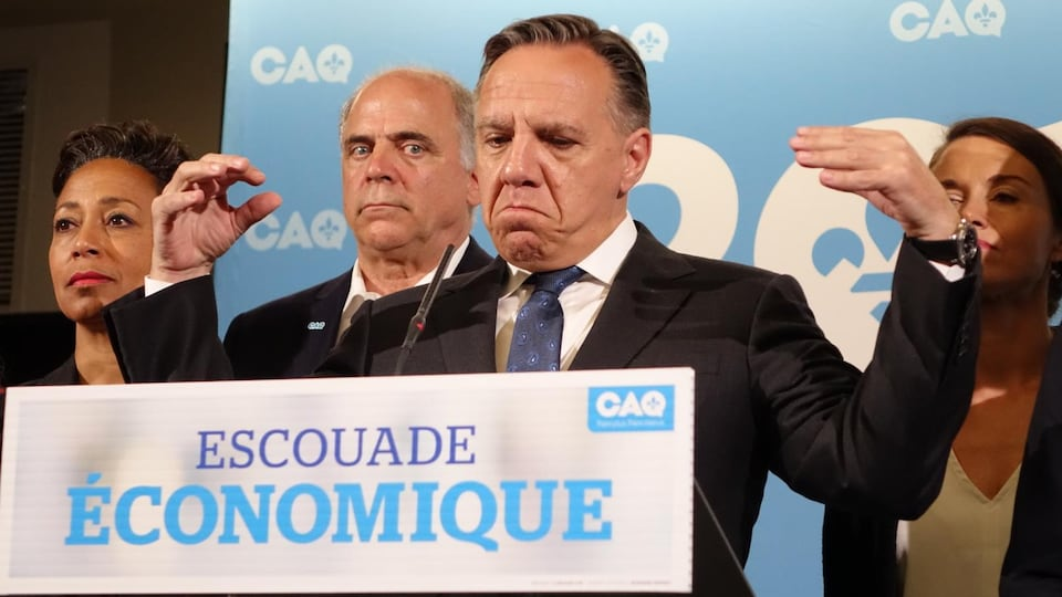 François Legault derrière un podium portant l'inscription Escouade économique, avec deux candidates et un candidat derrière lui.