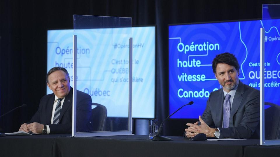 François Legault et Justin Trudeau assis à la table de la conférence de presse, séparés par des plexiglas.