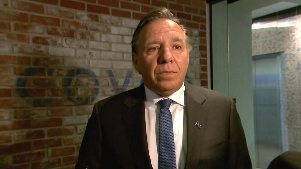 François Legault répond aux questions des journalistes lors d'une mêlée de presse en marge d'une visite au siège social de l'entreprise Coveo, à Québec.