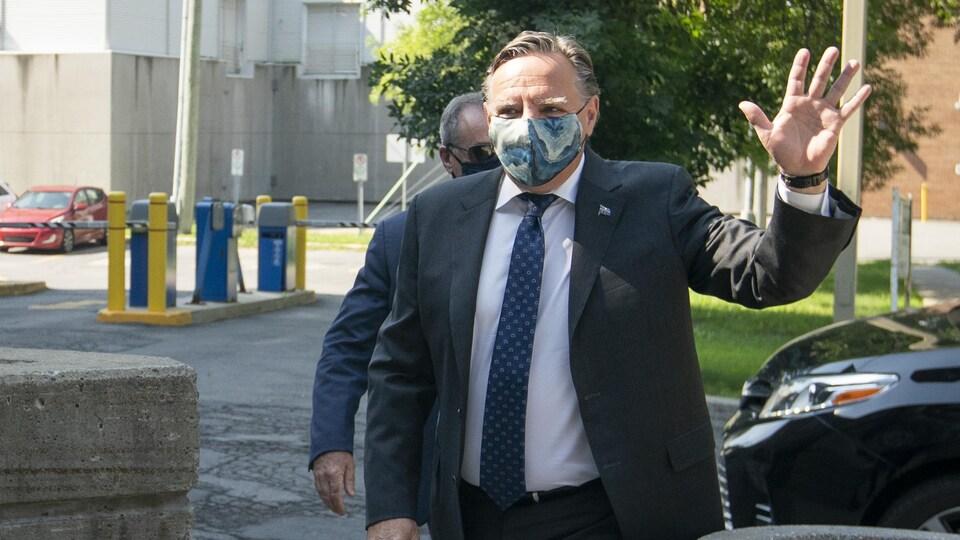 Le premier ministre François Legault portant un masque salue de la main gauche.