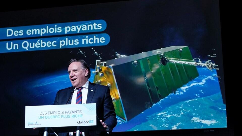 François Legault au micro avec, en arrière-plan, l'image d'un satellite dans l'espace.