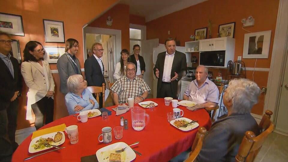 François Legault dans la cuisine avec des résidents et les candidats locaux de la CAQ