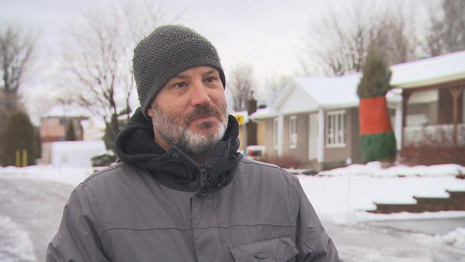 François Noël debout, qui donne une entrevue, dans une rue enneigée.