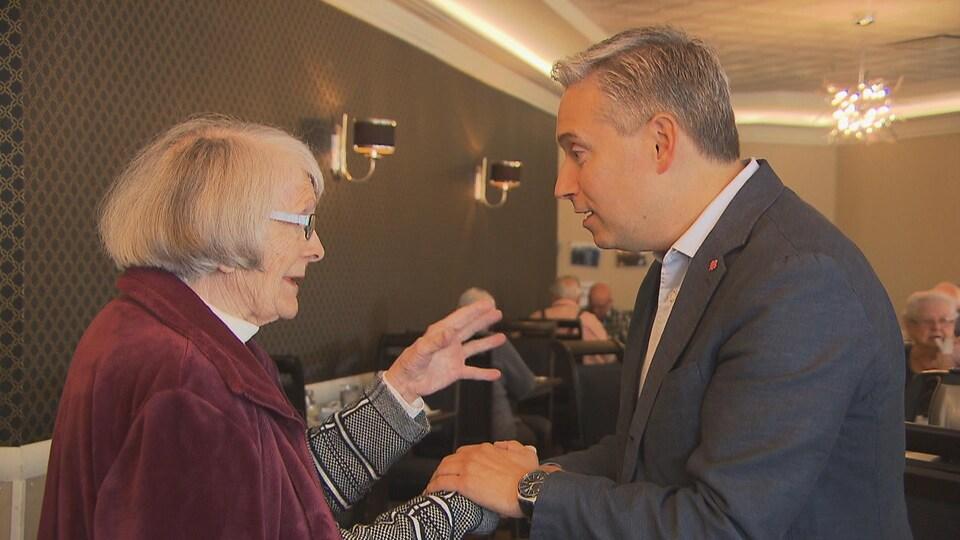Un homme tient les mains d'une dame âgée avec qui il discute.