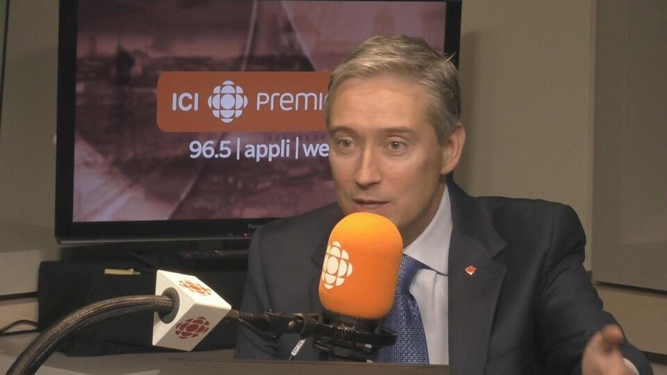 François-Philippe Champagne assis dans le studio radio de Trois-Rivières, avec un micro devant lui.