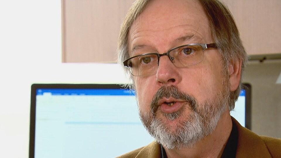 Un homme s'exprime avec un écran d'ordinateur en arrière-plan.