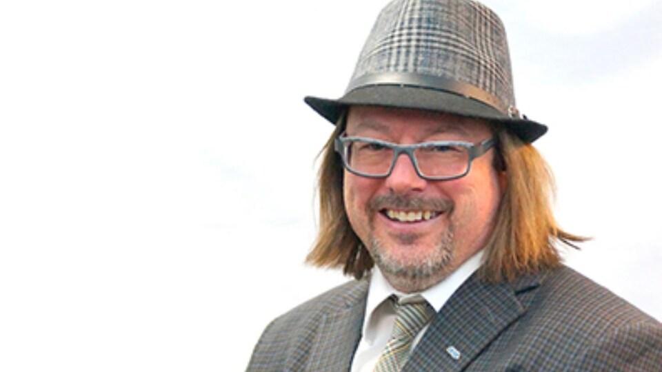 Photo professionnelle de François Rouleau, un homme avec un complet et un chapeau.