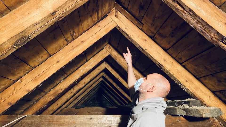 François Tremblay montre des poutres du toit.