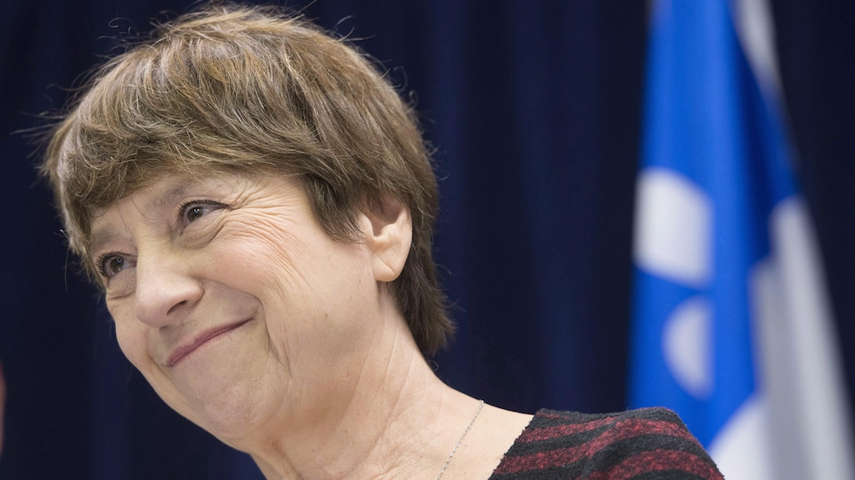 Françoise David en gros plan sourit alors qu'elle est est posée devant un drapeau du Québec.