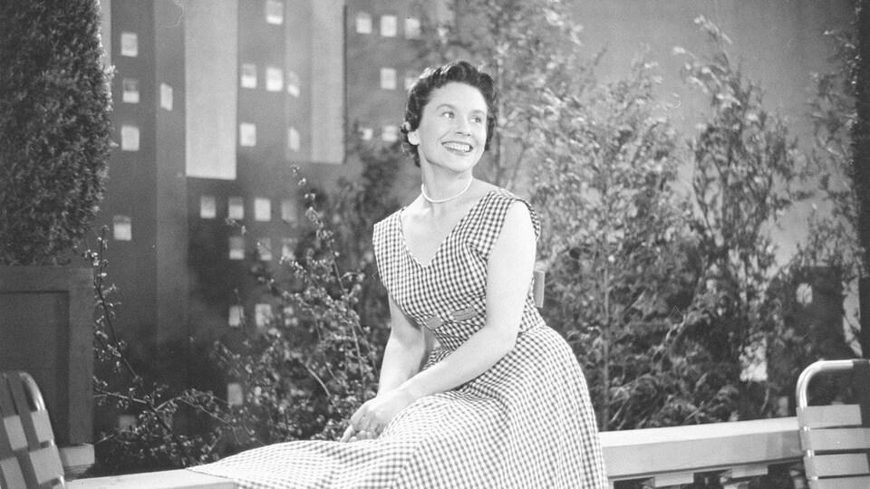 Françoise Faucher, souriante, assise élégamment dans un décor de belvédère.