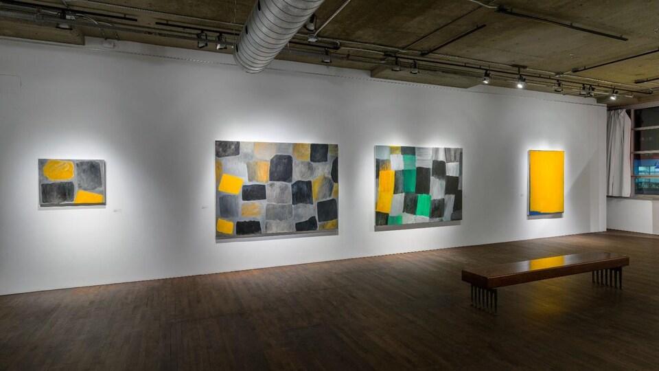 Quatre tableaux, dont trois de grande taille, sont affichés au mur.