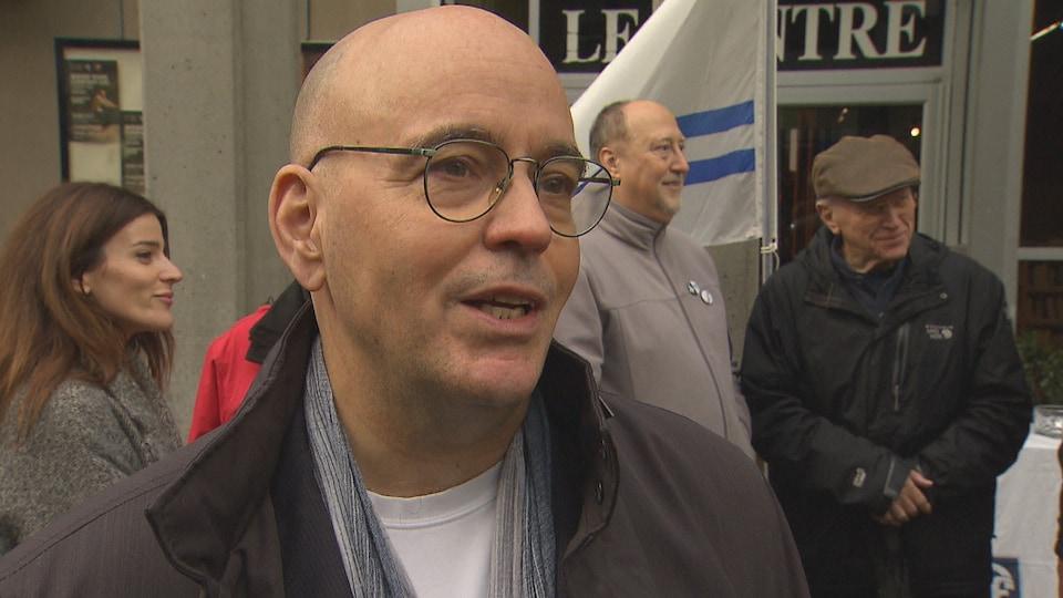 Robert Rothon manifeste devant un drapeau franco-colombien, dans une rue de Vancouver.