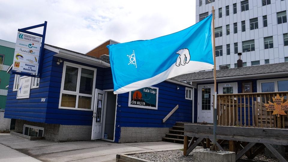 Un drapeau ténois flotte devant une maison bleue.