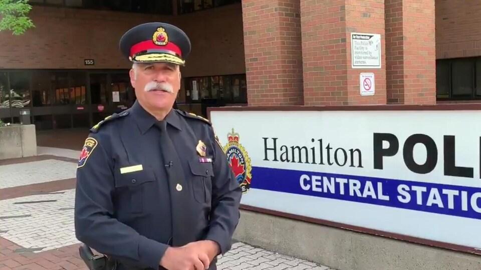 Le portrait d'un homme devant l'enseigne de la police de Hamilton