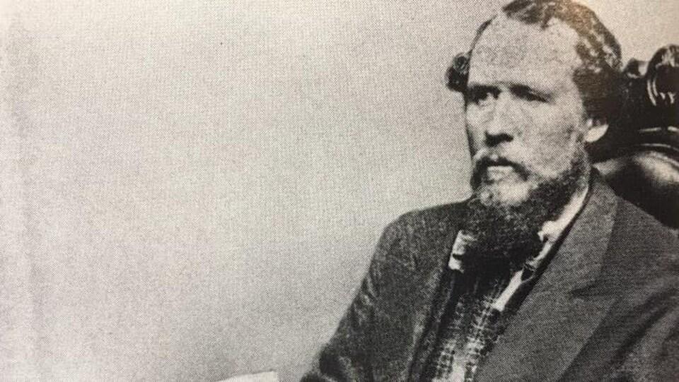 Francis Evans Cornish, le premier maire de Winnipeg, est assis dans un fauteuil.  Il porte une moustache et une barbe et a un regard éloigné de l'appareil photo.