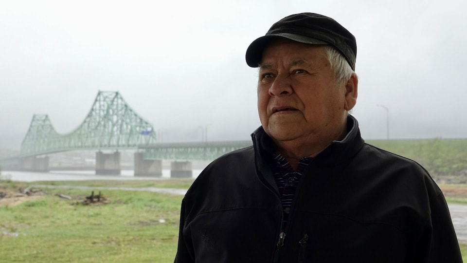 Frank Methot photographié avec le pont qui sépare Campbellton de Listuguj lors d'une journée pluvieuse.