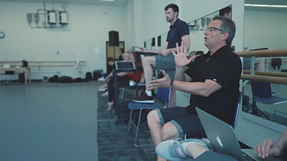 Jean Grand-Maitre donne des explications de sa chaise, en studio de danse.