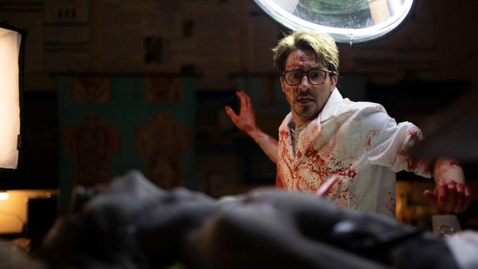 Un homme habillé d'un sarrau blanc, taché de sang, semble effrayé en regardant un homme couché sur sa table d'opération.