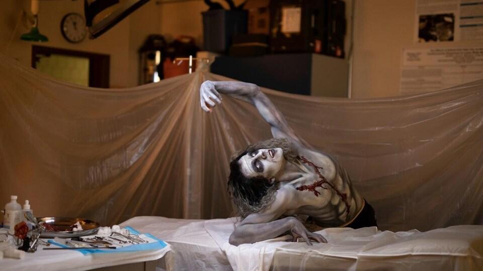 La créature de Frankenstein tente de se relever de sa table d'opération.