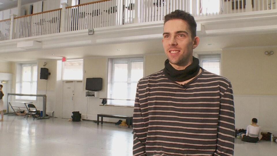 Un homme se tient debout dans un studio de danse.