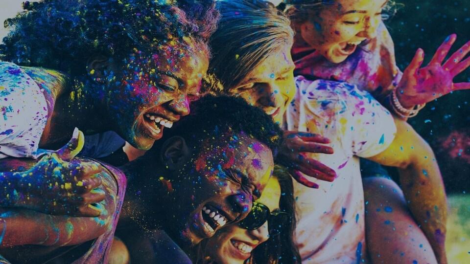 Des jeunes issus de l'immigration sourient en étant éclaboussés de peinture.
