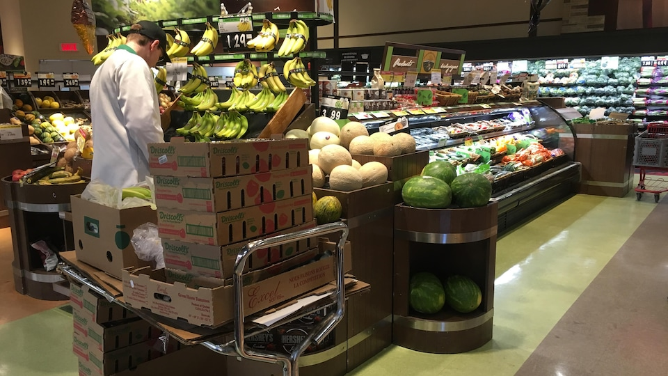 Un employé travaillant dans le département des fruits et légumes du IGA Yvon Haché.