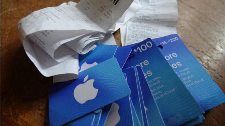 Des cartes-cadeaux iTunes et des reçus posés sur une table.