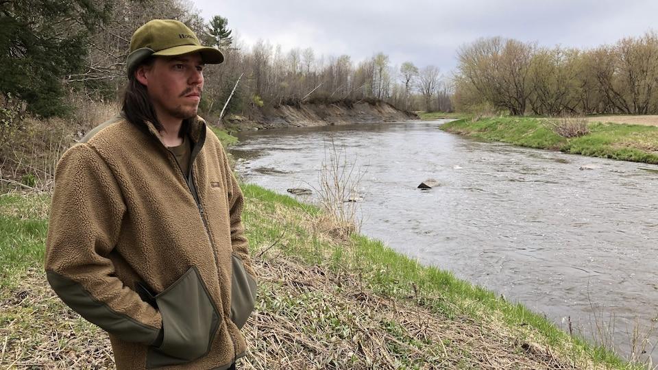 Fred Campbell, casquette sur la tête, regarde au loin sur le bord d'une rivière.