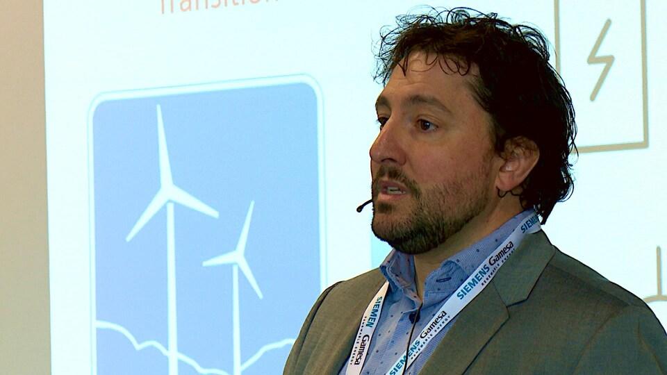 Homme devant une affiche d'éolienne.