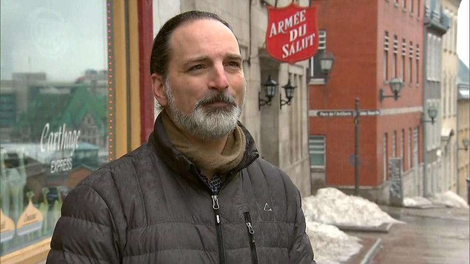 Frédéric Keck porte un manteau d'hiver et un foulard, il est devant un édifice de l'Armée du Salut