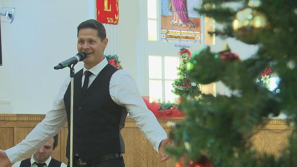 Le chanteur dans l'église, au micro, près d'un sapin de Noël.