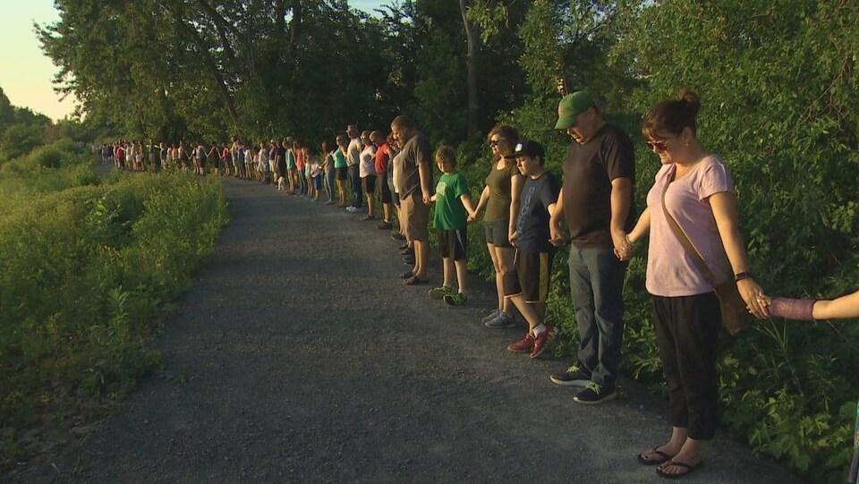 Plusieurs personnes forment une ligne sur un sentier en se tenant la main.