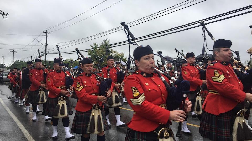 Des joueurs de cornemuse marchent en rang dans la rue, par une journée pluvieuse.
