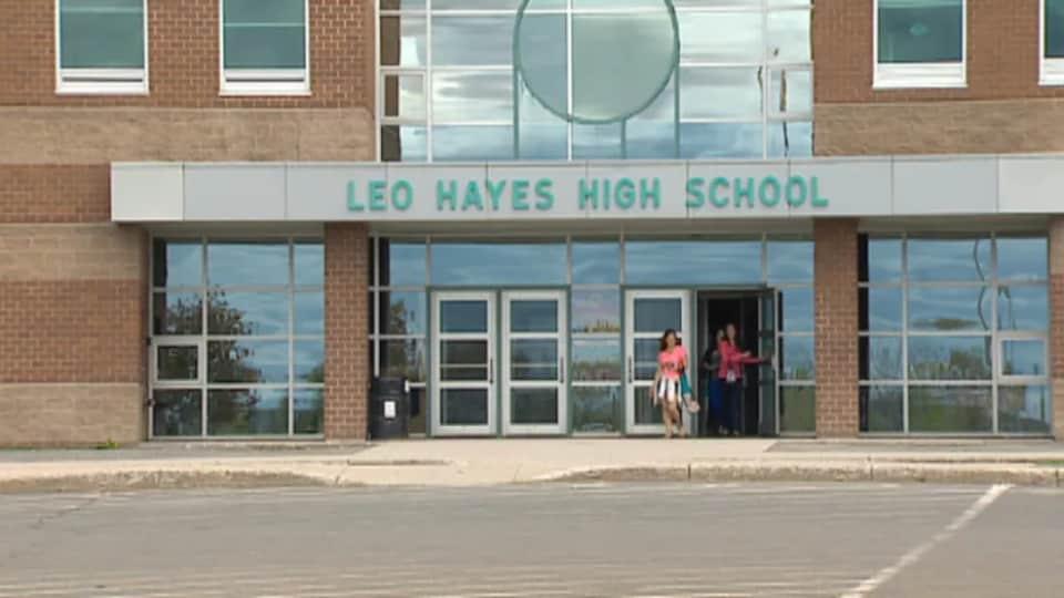 Trois personnes sortent de l'école.